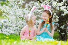 Zwei entzückende kleine Schwestern, die bunte Gummisüßigkeiten auf Ostern essen stockfoto