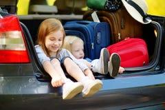 Zwei entzückende kleine Schwestern, die in einem Auto sitzen Stockfotografie