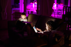 Zwei entzückende kleine Schwestern, die mit einer digitalen Tablette in einer Dunkelkammer spielen Lizenzfreies Stockfoto