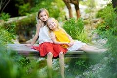 Zwei entzückende kleine Schwestern, die am warmen und sonnigen Sommertag lachen und umarmen stockfotografie