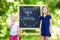 Zwei entzückende kleine Schwestern, die zurück zur Schule gehen Lizenzfreie Stockfotografie