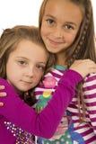 Zwei entzückende Mädchen, die tragende Winterpyjamas mit einem Spaßausdruck umarmen Stockfoto