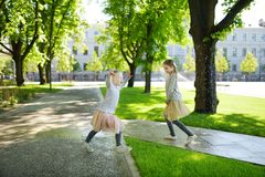 Zwei entzückendes Schwesterlachen und -betrieb am warmen und sonnigen Sommertag in einem Park lizenzfreie stockfotografie