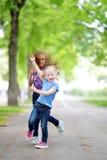 Zwei entzückende kleine Schwestern, die lachen und sich umarmen Stockfoto