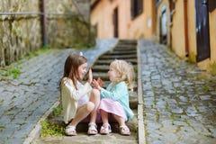 Zwei entzückende kleine Schwestern, die am warmen und sonnigen Sommertag lachen und sich umarmen Stockbild