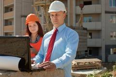 Zwei Erbauerarbeiten über die Baustelle lizenzfreie stockfotografie