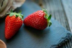 Zwei Erdbeeren auf einer rustikalen Steinplatte Lizenzfreies Stockfoto