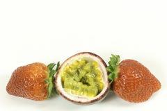 Zwei Erdbeeren und ein geschnittenes Maracuja auf Weiß stockfotografie