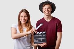 Zwei erfolgreiche junge halten weibliche und Mannesberühmte Produzenten oder -direktoren Filmscharnierventil, teilnehmen am Schie lizenzfreie stockfotos