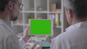 Zwei erfuhren männliche Doktoren, die Informationen über die Tablette überprüfen und besprachen sich Konzept von Medizin, von Ges stock footage