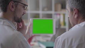 Zwei erfuhren männliche Doktoren, die Informationen über die Tablette überprüfen und besprachen sich Konzept von Medizin, von Ges stock video footage