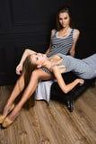 Zwei ernste Freundinschwestern auf schwarzem Hintergrund Stockfoto