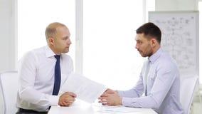 Zwei ernste Geschäftsmänner mit Diagrammen im Büro stock video footage