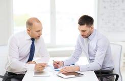Zwei ernste Geschäftsmänner mit Tabletten-PC im Büro lizenzfreie stockfotografie