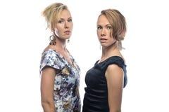 Zwei ernste Schwestern auf weißem Hintergrund Stockbild