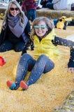 Zwei erwachsene Frauen begraben sich in einer Maisgrube an einem Maislabyrinth lizenzfreies stockbild