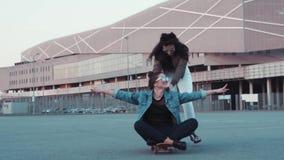 Zwei erwachsene Frauen, die Spaß, das man haben, sitzt auf dem Skateboard, anders zieht sie, sie lachen Glückliche Zeit, seiend stock video