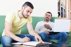 Zwei erwachsene Männer mit Laptop zuhause Lizenzfreie Stockfotografie