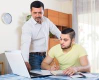 Zwei erwachsene Männer mit Laptop zuhause Stockfotografie