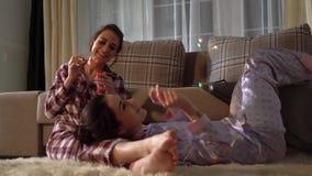 Zwei erwachsene Schwesterzwillinge, welche die Schlagblasen des Spaßes tragen hübsche pajams auf dem Hintergrund des gemütlichen  stock footage