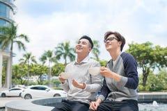 Zwei erwachsener Mannesfreunde sitzen die Unterhaltung über Kaffee außerhalb des Cafés stockbilder
