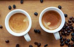 Zwei Espressokaffee in den kleinen weißen Schalen, mit einem Kaffeebohnerest Stockfotos