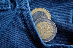 Zwei Euromünzen mit einer Bezeichnung von Euro 1 und 2 in der Tasche von blauen Denimjeans Stockbilder