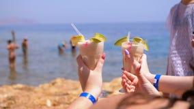 Zwei exotische Cocktails in den Händen von Mädchen am Hintergrund des Meeres und Strand in Ägypten stock video