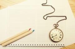 Zwei färbten hölzerne Bleistifte, Notizbuch und alte Taschenuhr Stockfotos