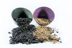 Zwei färbten Schalen mit schwarzen Samen und zogen Samen ab Stockfotos