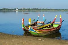 Zwei färbten traditionelle birmanische Boote auf dem Ufer von Taung Tha Man See Amarapura, Myanmar Stockbild