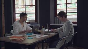 Zwei IT-Fachmänner, die am Arbeitsplatz sitzen stock video