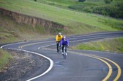 Zwei Fahrradmitfahrer auf landwirtschaftlicher Straße Stockfotografie
