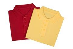Zwei falteten die roten und gelben Polohemden, die auf Weiß lokalisiert wurden lizenzfreies stockfoto