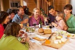 Zwei Familes, das Mahlzeit im alpinen Chalet genießt Stockfotografie