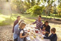 Zwei Familien, die ein Picknick zusammen an einem Tisch in einem Park haben stockfoto