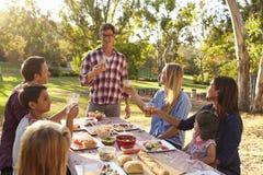 Zwei Familien, die einen Toast am Picknick an einem Tisch in einem Park machen stockfotos