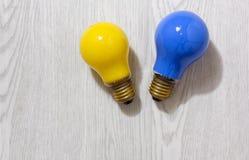 Zwei farbige Glühlampen auf einem hölzernen Hintergrund Lizenzfreies Stockbild
