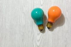 Zwei farbige Glühlampen auf einem hölzernen Hintergrund Stockfotos