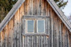Zwei Fenster auf einem verwitterten und gealterten Blockhaus Stockfoto