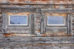 Zwei Fenster auf einem verwitterten und gealterten Blockhaus Lizenzfreie Stockfotos