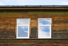 Zwei Fenster auf hölzerner Wand Lizenzfreie Stockfotos