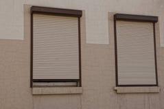 Zwei Fenster geschlossen durch Rollenfensterläden auf einer braunen Wand lizenzfreie stockfotografie