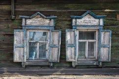 Zwei Fenster mit dem hölzernen geschnitzten Architrav im alten Holzhaus in der alten russischen Stadt stockfotografie