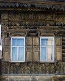 Zwei Fenster mit dem hölzernen geschnitzten Architrav im alten Holzhaus in der alten russischen Stadt stockfoto