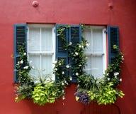 Zwei Fenster, rote Wand, schwarze Fensterläden Lizenzfreie Stockfotografie