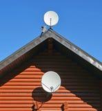 Zwei Fernsehsatellitenschüsseln auf Wand und Dach des Holzhauses lizenzfreie stockfotos