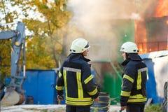 Zwei Feuerwehrmänner auf einem Feuer, auf dem Hintergrundfeuer Stockfoto