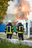 Zwei Feuerwehrmänner auf einem Feuer, auf dem Hintergrundfeuer Lizenzfreies Stockbild