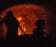 Zwei Feuerwehrmänner, die ein Feuer in Angriff nehmen lizenzfreies stockbild